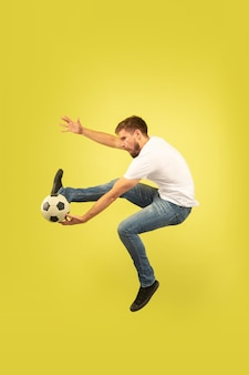 Retrato de corpo inteiro de homem pulando feliz isolado em fundo amarelo. modelo masculino caucasiano com roupas casuais. liberdade de escolha, inspiração, conceito de emoções humanas. jogando futebol na corrida.