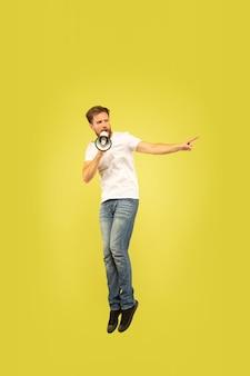 Retrato de corpo inteiro de homem pulando feliz isolado em fundo amarelo. modelo masculino caucasiano com roupas casuais