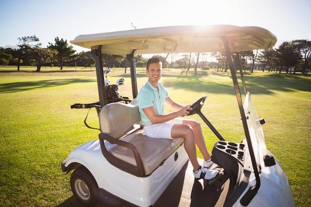 Retrato de corpo inteiro de homem sentado no carrinho de golfe