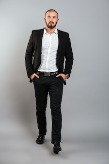 Retrato de corpo inteiro de homem sério em terno profissional posando na câmera com as mãos nos bolsos, isolado sobre a parede cinza
