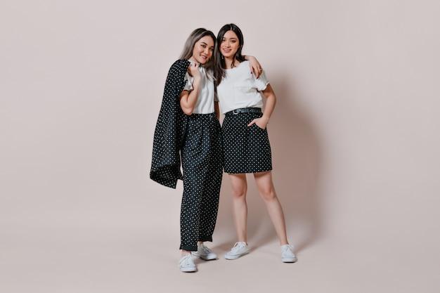 Retrato de corpo inteiro de irmãs com roupas semelhantes e bolinhas posando contra uma parede isolada