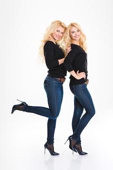 Retrato de corpo inteiro de irmãs gêmeas felizes posando isolado em um fundo branco