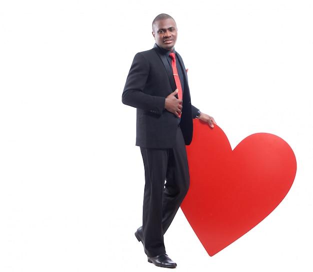 Retrato de corpo inteiro de jovem africano na suíte preta e gravata vermelha, apoiando-se no grande coração vermelho decorado