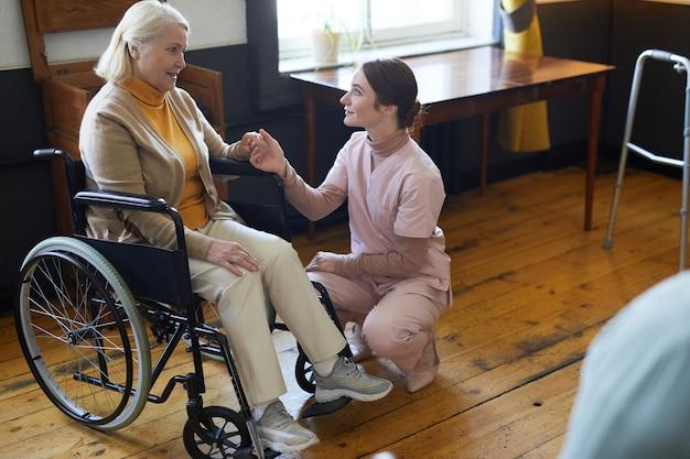 Retrato de corpo inteiro de jovem ajudando mulher sorridente sênior em cadeira de rodas em um policial de lar de idosos.