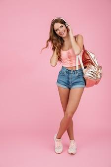 Retrato de corpo inteiro de jovem alegre no desgaste do verão com mochila, ouvindo música em fones de ouvido brancos