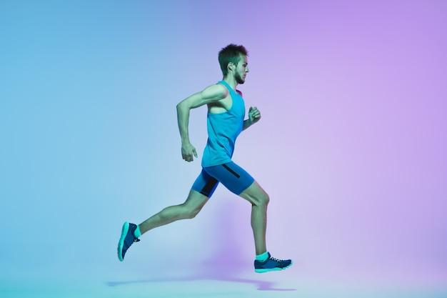 Retrato de corpo inteiro de jovem ativo caucasiano correndo, correndo na parede de néon