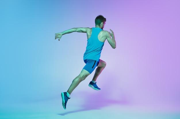 Retrato de corpo inteiro de jovem ativo caucasiano correndo, correndo