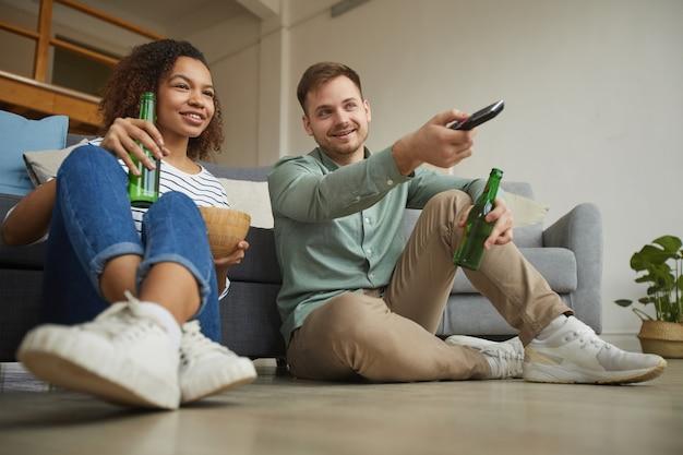 Retrato de corpo inteiro de jovem casal mestiço assistindo tv em casa e bebendo cerveja enquanto está sentado no chão de um apartamento aconchegante