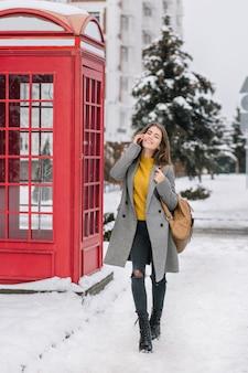 Retrato de corpo inteiro de jovem elegante com casaco cinza e calças rasgadas, falando no telefone, andando pela rua com neve. foto de uma mulher deslumbrante em pé perto da cabine vermelha e segurando um smartphone.