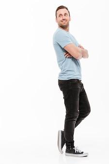 Retrato de corpo inteiro de jovem em casual posando com amplo sorriso e braços cruzados, olhando para trás