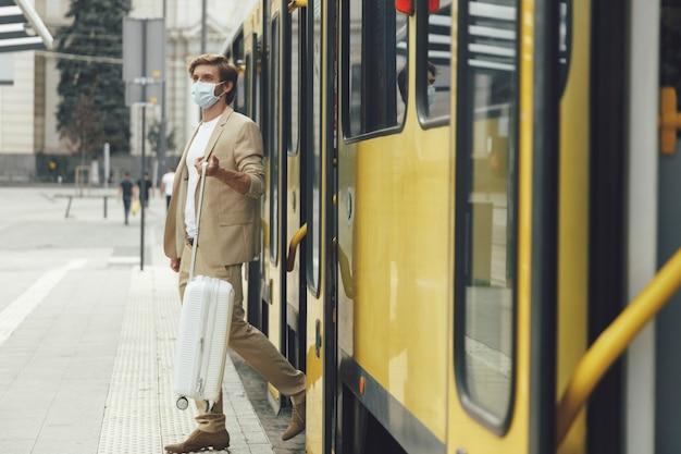 Retrato de corpo inteiro de jovem empresário em traje formal com mala branca, descendo do bonde