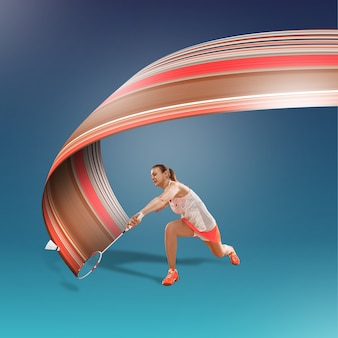 Retrato de corpo inteiro de jovem jogando badminton isolado sobre fundo azul. estilo de vida saudável. fitness, esporte, ação, conceito de publicidade. modelo feminino em movimento ou movimento. desenho abstrato.