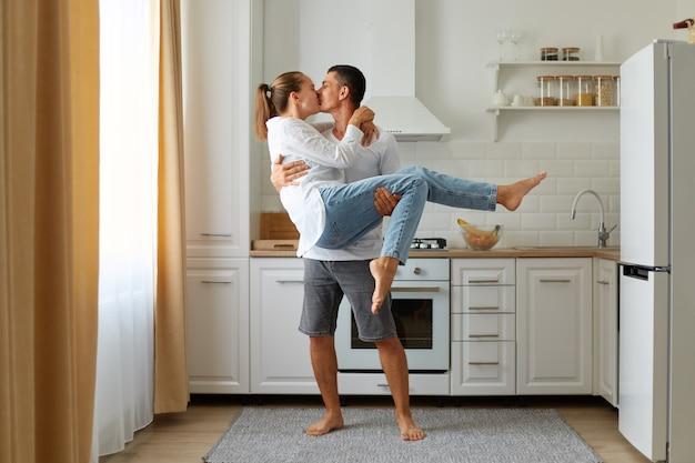 Retrato de corpo inteiro de jovem segurando sua linda namorada nos braços em pé na cozinha em casa e beijá-la. ambos se olham, com amor e sentimentos românticos.