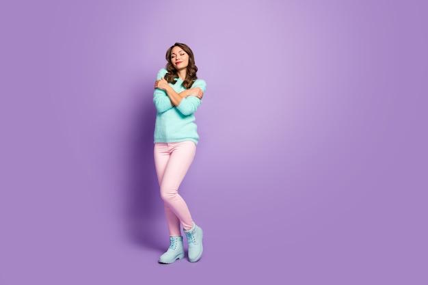 Retrato de corpo inteiro de linda garota doce positiva ter pulôver de lã turquesa quente abraçar a si mesma desfrutar de olhos próximos usar roupa de boa aparência.