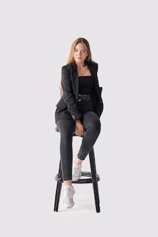 Retrato de corpo inteiro de linda jovem sentado na cadeira alta em jeans preto e jaqueta sobre fundo cinza