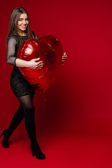Retrato de corpo inteiro de linda morena alegre em vestido preto e botas de cano altas andando com grande balão inflável vermelho em forma de coração.