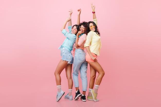 Retrato de corpo inteiro de lindas garotas em pé com as mãos para cima e rindo com o interior rosa. magnífica senhora africana posando entre amigos internacionais em roupas casuais.