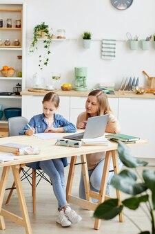 Retrato de corpo inteiro de mãe carinhosa, ajudando a linda garota fazendo a lição de casa ou estudando à mesa no interior aconchegante da casa, copie o espaço
