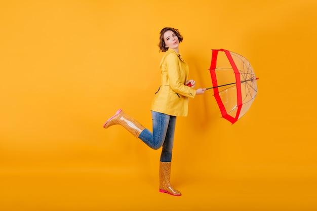 Retrato de corpo inteiro de menina bem torneada em sapatos de borracha dançando com guarda-sol vermelho. senhora encaracolada na jaqueta amarela em pé sobre uma perna e segurando o guarda-chuva.