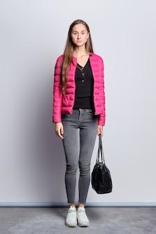 Retrato de corpo inteiro de menina bonita em jaqueta e calça jeans em pé perto da parede com bolsa de mão