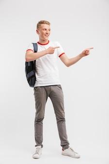Retrato de corpo inteiro de menino estudante vestindo roupas casuais e mochila, apontando o dedo de lado na copyspace, isolado sobre o branco