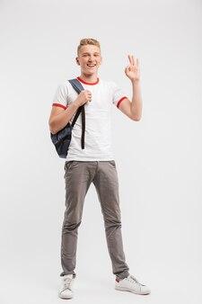 Retrato de corpo inteiro de menino estudante vestindo roupas casuais e mochila gesticulando bem ou sinal de ok, isolado sobre o branco