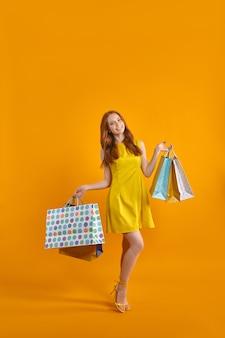Retrato de corpo inteiro de moça modelo animado carrega muitos pacotes desfrutando de compras no exterior usando t ...
