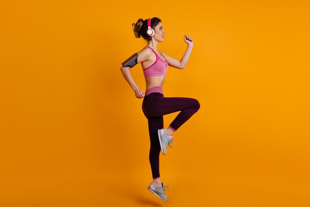 Retrato de corpo inteiro de modelo feminina fazendo exercícios aeróbicos