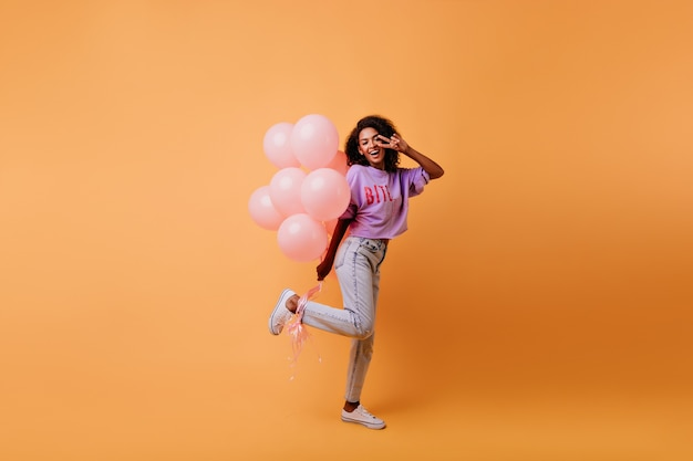 Retrato de corpo inteiro de mulher africana refinada se preparando para o evento. aniversariante sonhadora dançando com balões.