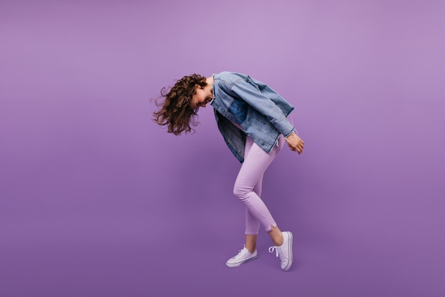 Retrato de corpo inteiro de mulher ativa na moda. tiro interno de menina caucasiana com corte de cabelo curto dançando.