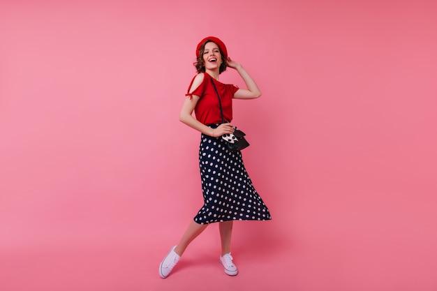 Retrato de corpo inteiro de mulher caucasiana bem-humorada dançando na boina francesa. foto interna da garota espetacular positiva com cabelo encaracolado.