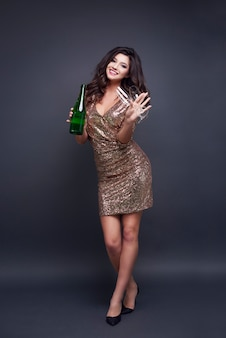 Retrato de corpo inteiro de mulher com taça de champanhe e garrafa