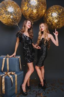 Retrato de corpo inteiro de mulher de cabelos castanhos magro em sapatos pretos, posando com balões brilhantes antes da festa. irmãs bonitas de bom humor se divertindo juntas durante a festa.