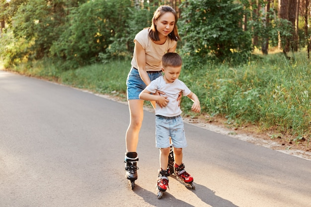 Retrato de corpo inteiro de mulher e filho andando de patins juntos, mãe ensinando a patinar seu filho, lindo menino aprendendo andar de patins.