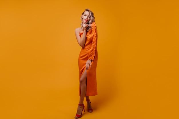 Retrato de corpo inteiro de mulher elegante e feliz com sapatos vermelhos