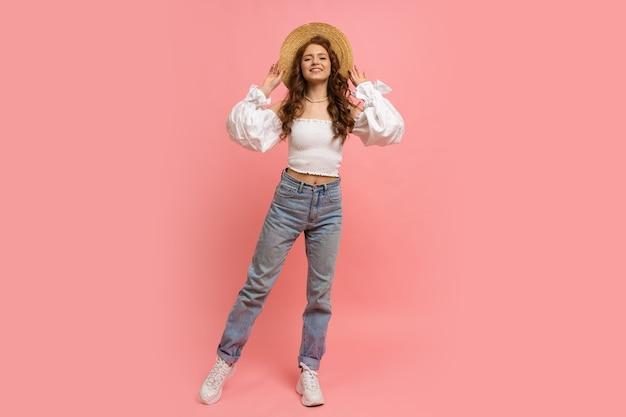 Retrato de corpo inteiro de mulher em elegante top de linho com mangas balão e jeans azul posando em rosa