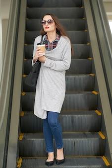 Retrato de corpo inteiro de mulher em óculos de sol descendo a escada rolante com café para viagem