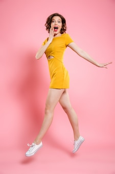 Retrato de corpo inteiro de mulher feliz saiu no elegante vestido amarelo ao saltar sobre rosa
