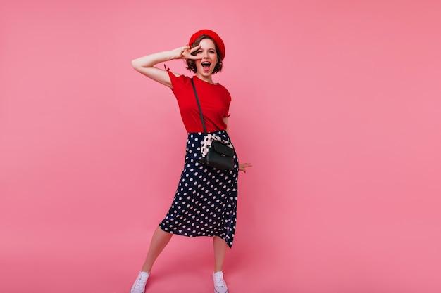 Retrato de corpo inteiro de mulher francesa animada, se divertindo. jocund senhora caucasiana na boina vermelha dançando.