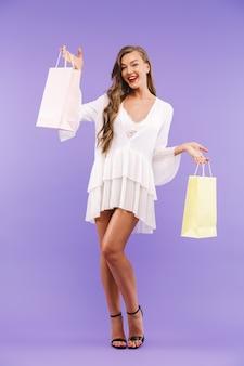 Retrato de corpo inteiro de mulher glamourosa, vestido branco, segurando sacolas de papel com compras
