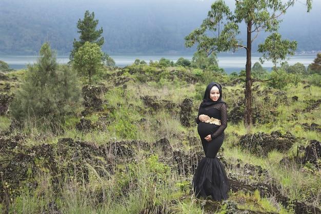 Retrato de corpo inteiro de mulher grávida asiática usando hijab com paisagem natural