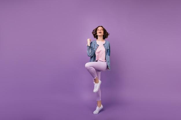 Retrato de corpo inteiro de mulher incrível satisfeita em sapatos brancos. menina caucasiana usa roupas casuais, dançando.