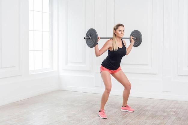 Retrato de corpo inteiro de mulher jovem atlética bonita fisiculturista em shorts rosa e blusa preta, fazendo agachamentos e se exercitando na academia com a barra na parede branca. indoor, studio shot,