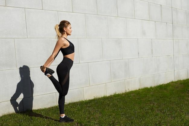 Retrato de corpo inteiro de mulher jovem e atraente fazendo exercícios físicos ao ar livre na grama verde num dia ensolarado de verão, alongando os músculos quadríceps, vestida com uma roupa preta elegante. esportes e bem-estar