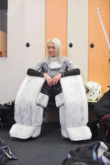 Retrato de corpo inteiro de mulher jovem e esportiva usando uniforme completo de hóquei sentado no banco