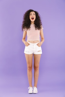 Retrato de corpo inteiro de mulher jovem feliz com cabelos cacheados em streetwear verão sorrindo e olhando para cima