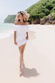 Retrato de corpo inteiro de mulher loira romântica caminhando pela praia com um sorriso. mulher de cabelos louros feliz relaxando em um resort tropical.