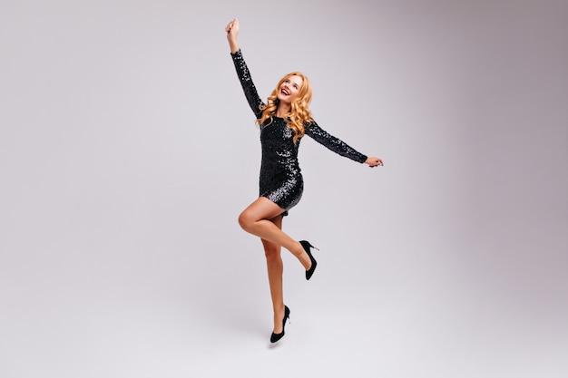Retrato de corpo inteiro de mulher magra satisfeita em sapatos de salto alto. foto interna de uma garota caucasiana entusiasmada.