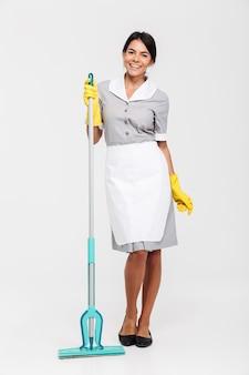 Retrato de corpo inteiro de mulher morena alegre em luvas de uniforme e borracha em pé e segurando o esfregão