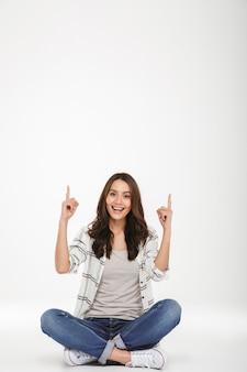 Retrato de corpo inteiro de mulher satisfeita em roupas casuais, sentado em posição de lótus no chão e apontando os dedos para cima, isolado sobre a parede branca